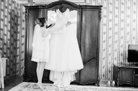 hangers: Portrait of a beautiful bride posing with her dress on a hanger in the room. Black and white photo. Stock Photo