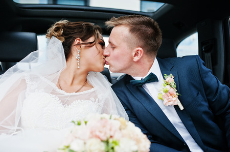 Beautiful wedding couple sitting in the car, looking into each others eyes and kissing. Stock Photo