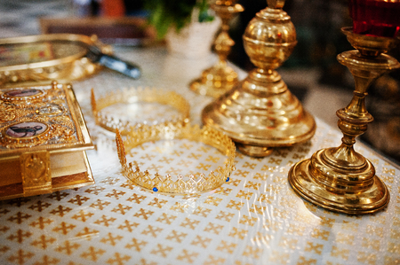 new testament: Close-up photo of crowns laying on the table next to the candlesticks and bible in the church. Stock Photo