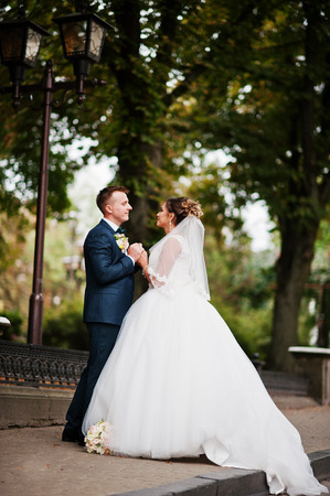 Good-looking newly married couple walking and enjoying each others company in the park on a bright and sunny wedding day.
