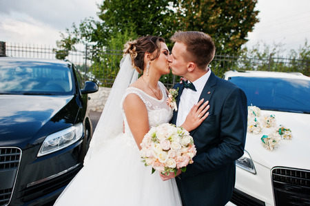 Gorgeous wedding couple enjoying each others company next to wedding suvs. Stock Photo