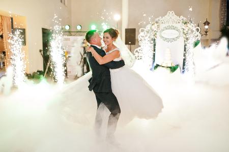 Schöne Hochzeitspaar tanzt ihren ersten Tanz in der riesigen Halle mit schweren Rauch, verschiedene Lichter und Leute, die sie betrachten.