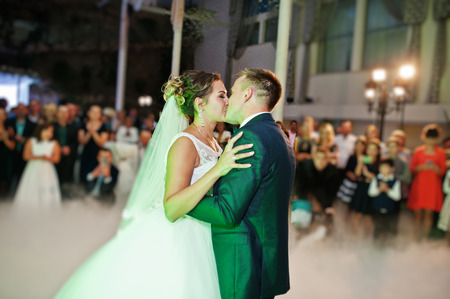 Beautiful wedding couple dancing their first dance in the huge hall with heavy smoke, different lights and people looking at them.