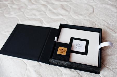 Elegant white and black wedding photobooks or photo albums on the white sofa.