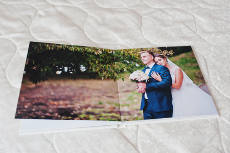 Pages of wedding photobook or wedding album on white sofa background. Stock Photo