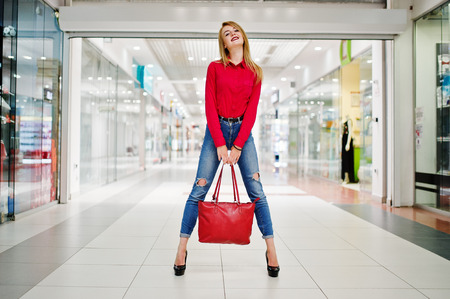 comprando zapatos: Portrait of a beautiful woman wearing red blouse, casual jeans and black high heels poses with red leather handbag in huge shopping mall.