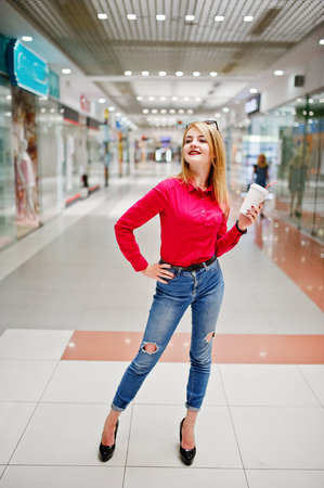 Portrait of a gorgeous woman in red blouse and jeans holding a cup of coffee in a shopping mall. Stock Photo