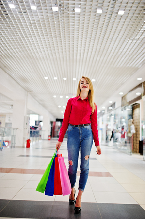 Portrait of a stunning young woman in red blouse, ripped casual jeans and high heels posing with shopping bags in mall.