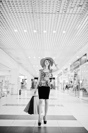 Portrait of an attractive young woman in leopard blouse, black skirt posing with a hat and shopping bags. Black and white photo. Stock Photo