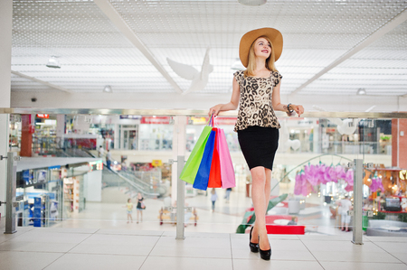 Portrait of an attractive young woman in leopard blouse, black skirt posing with a hat and shopping bags.