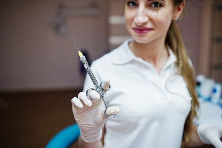 Portrait of a female dentist in white coat posing with syringe filled with anesthesia in a dental cabinet.