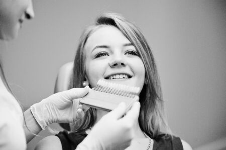 figuring: Talented female dentist figuring out what is the matching teeth color for her patient. Black and white photo.