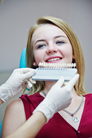 figuring: Talented female dentist figuring out what is the matching teeth color for her patient. Stock Photo