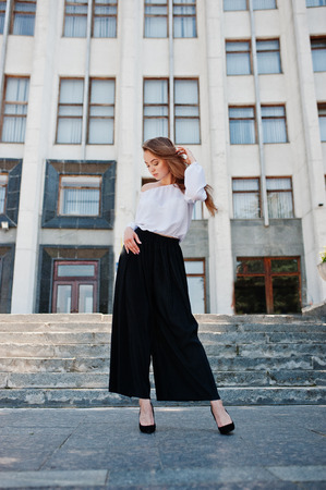 Portrait of a fabulous young successful woman in white blouse and broad black pants posing on the stairs with a huge white building on the background.