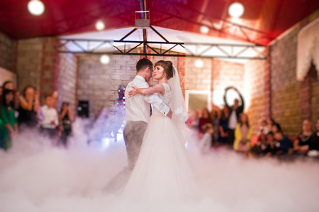 Wedding couple dancing their first wedding dance with heavy smoke and different lights in the restaurant full of guests.