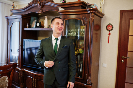 affable: Portrait of a handsome groom posing on his own in the room on a wedding day.