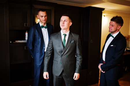 affable: Handsome groom posing with his groomsmen in the room before a wedding.