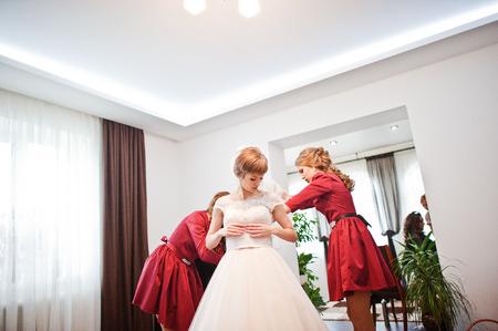Las hermosas damas de honor ayudan a la novia a prepararse para la ceremonia de su boda. Foto de archivo