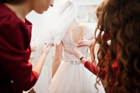 Bridesmaids helping bride to tie a bow on a wedding dress.