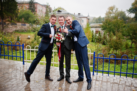 Handsome groom and his fellow groomsmen having fun outside on a rainy wedding day.