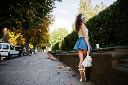De krullende modieuze meisjesslijtage op jeansrok, blouse en glazen stelde bij straat van stad met kop van koffie. Stockfoto