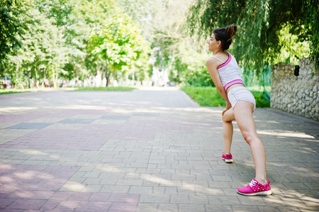 Sport girl wear on white shorts and shirt doing exercise at park. Stock Photo