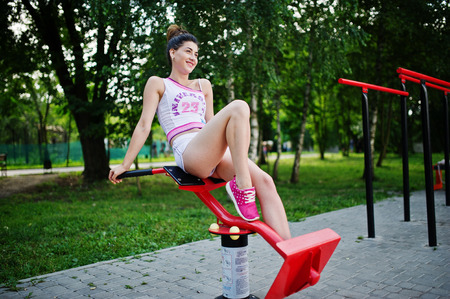 Sport girl wear on white shorts and shirt doing exercises on simulators outdoor at park.