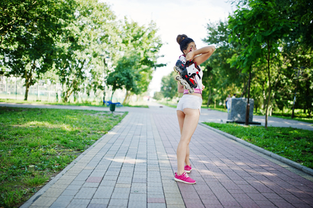 Sport girl wear on white shorts and shirt with roller skates at park.