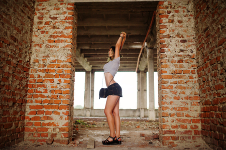 Girl wear on shorts at abadoned factoty with brick walls.