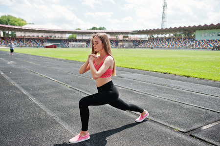Fitness sporty girl in sportswear at stadium. Happy sexy woman workout and doing exercises.