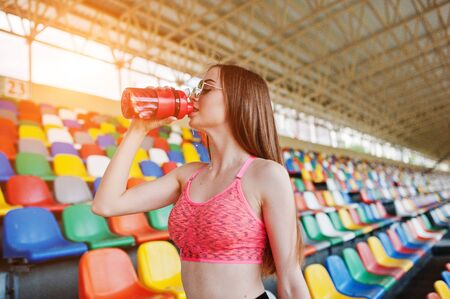Fitness sporty girl in sportswear and sunglasses posed at stadium tribune. Happy sexy woman drinking water from bottle.