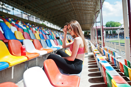 Fitness sporty girl in sportswear and sunglasses posed at stadium tribune