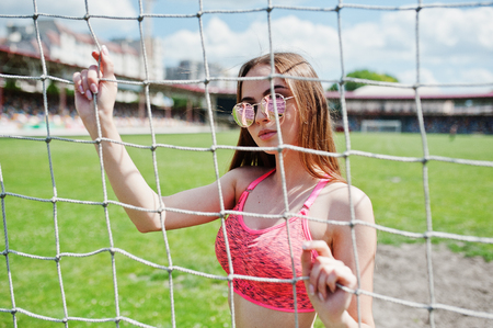 cross legs: Fitness sporty girl in sportswear and sunglasses posed at stadium football gates outdoor sports.
