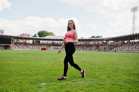 Fitness sporty girl in sportswear at stadium. Happy sexy woman with sport bottle mockup.