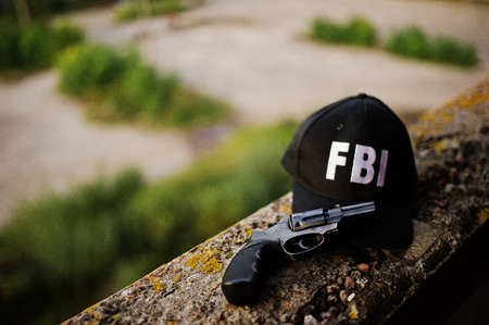 FBI cap with revolver and handcuff.