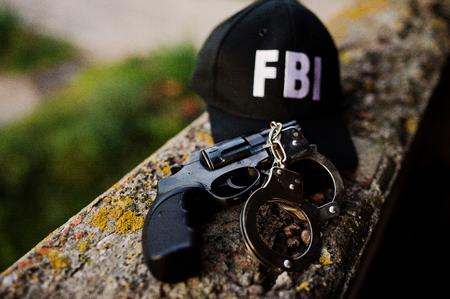 FBI-pet met revolver en handboei.