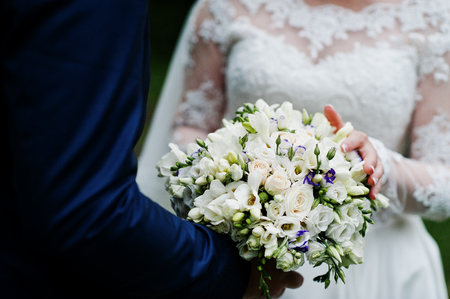 Close-up photo of a wedding bouquet in grooms hands.