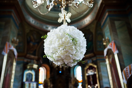 Floral decoration made of roses hanging from the chandelier in the church.
