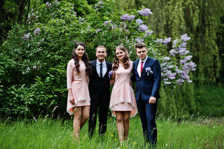 Bridesmaids in pink dresses posing with handsome groomsmen in tuxedos in the park with blossoming trees in the background. Stock Photo