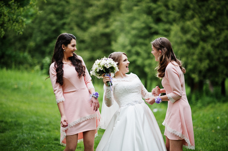 Attractive bride posing and having fun with two her bridesmaids in the park on a sunny spring wedding day.