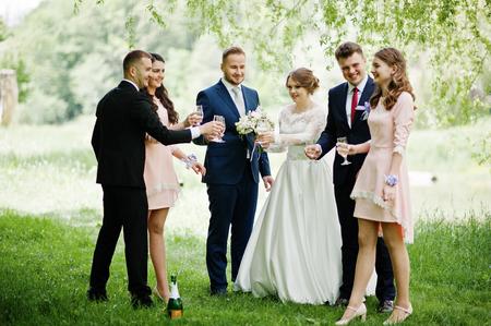 웨딩 커플, 신부 들러리 및 신랑들 샴페인을 마시는 축제 결혼식을 하루에 공원에서.