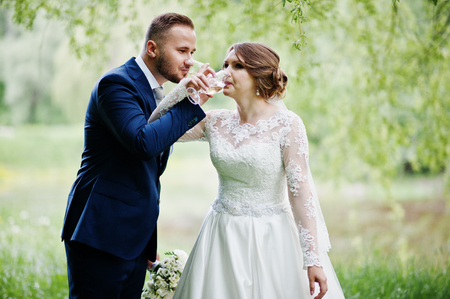 Newly married wedding couple drinking champagne in forest or park.
