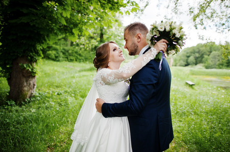 Close-up photo of a wedding couple looking each other in the eyes in nature. Stock Photo