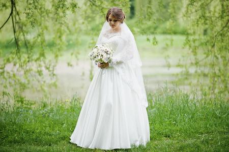 花束彼女自身に屋外でポーズ美しい若い花嫁の肖像画。