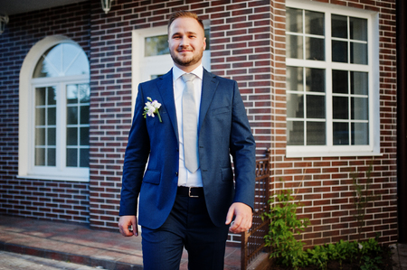 Portrait of a handsome young groom posing with a brick house on the background. Stock Photo