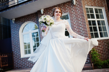 Portrait of an attractive bride spinning in front of a house with a wedding bouquet.