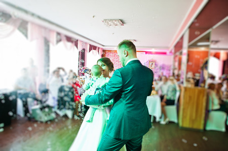 Fantastic young beautiful wedding couple dancing in the restaurant with their little baby. Stock Photo