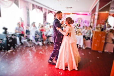 Beautiful wedding couple performing their first dance in the restaurant with different lights and bubbles and guests on the background. Stock Photo