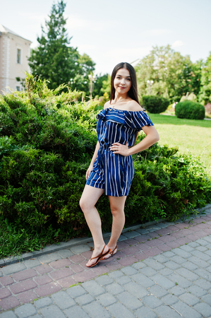 Gorgeous brunette girl at street of city wear on blue striped dress.