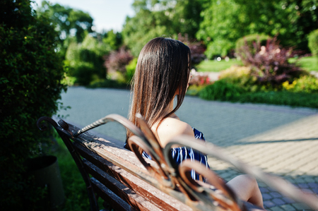 Gorgeous brunette girl sitting on bench at street of city wear on blue striped dress. Stock Photo